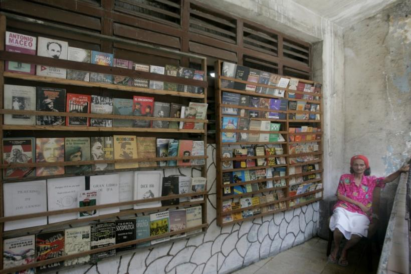 Woman offers used books for sale at a street stall in Havana