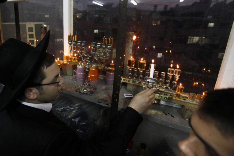 A Jewish seminary student lights a candle for Hanukkah in Ashdod