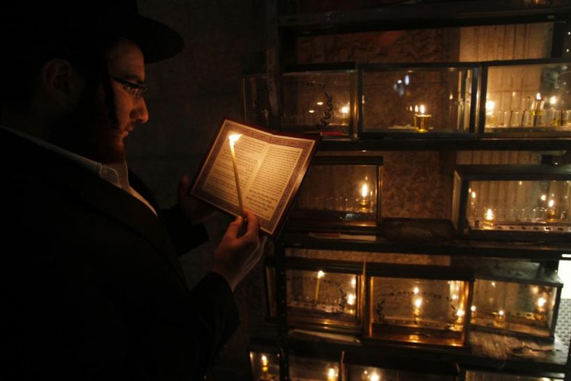 Jewish seminary student Mayer Engel recites a prayer as he lights a candle for the Hanukkah in Jerusalem's Mea Shearim neighbourhood