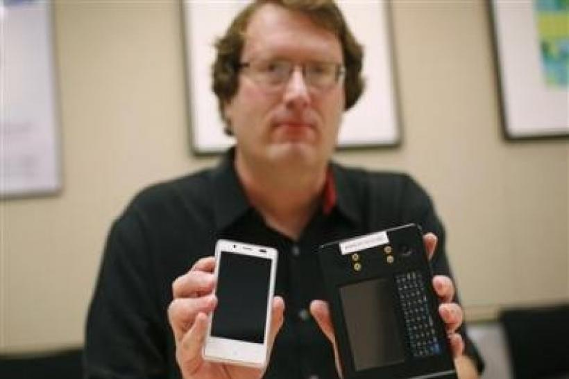Mike Bell, co-general manager of Intel's new Mobile and Communications Group, holds an Android reference smartphone (L) he designed, next to a reference phone Intel used to demonstrate the chip at earlier stages, during an interview at the company&#0
