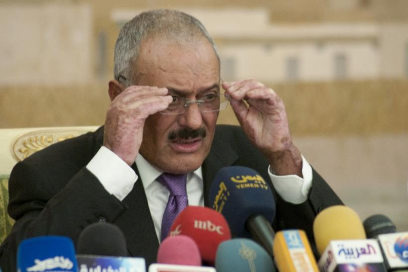 Yemen's outgoing President Ali Abdullah Saleh adjusts his spectacles during a news conference in Sanaa