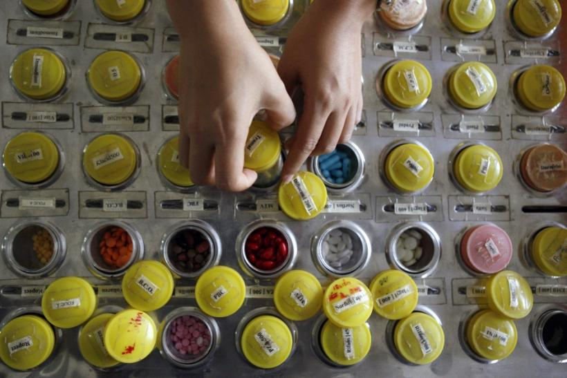 A nurse prepares doses of brand name and generic HIV-AIDS drugs for patients