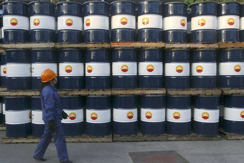 An engineer walks past piles of oil tanks at a PetroChina's oil refinery in Lanzhou