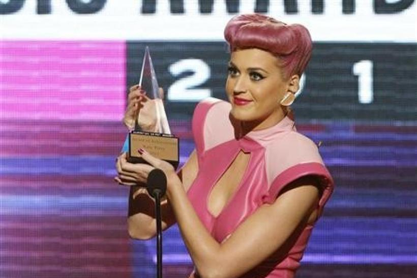 Singer Katy Perry holds up her special achievement award, which she received for being the first female pop artist with five number one hits from one album, at the 2011 American Music Awards in Los Angeles