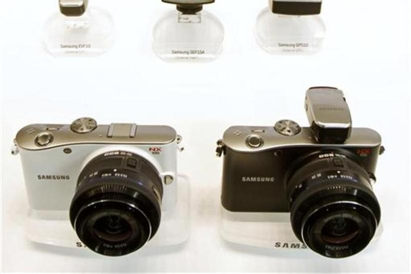 Samsung Electronics' new camera model NX100s and accessories are placed on a desk during a media preview in Seoul