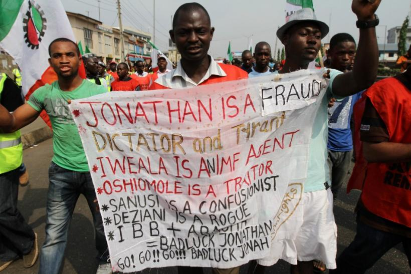 A man holds a banner as protesters march through a road on the third day of a protest against a removal of fuel subsidies in Lagos