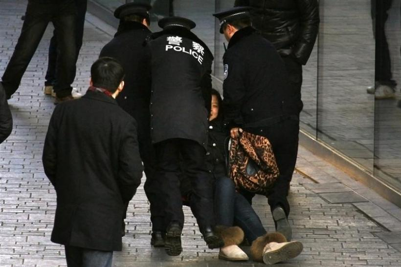 A woman is dragged away by police after she refused to leave from the front of the Apple store in the Beijing district of Sanlitun