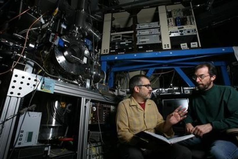 Sandia combustion researchers Craig Taatjes and David Osborn (R) discuss data found from the detection and measurement of Criegee intermediate reactions in front of the apparatus was used to make the measurements, which researchers believe will substantia