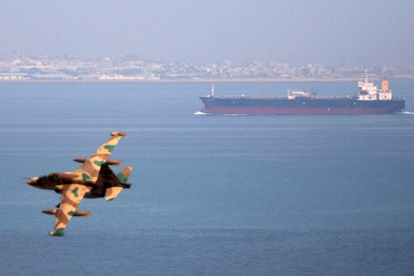 An Iranian military fighter plane flies past an oil tanker during naval maneuvres in the Persian Gulf and Sea of Oman April 5, 2006.