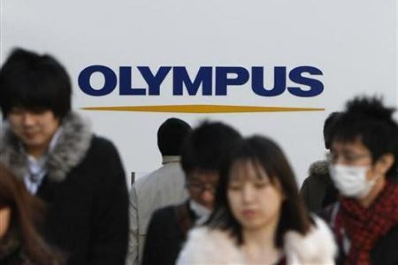People walk past a signboard of Olympus Corp outside its showroom in Tokyo January 12, 2012.