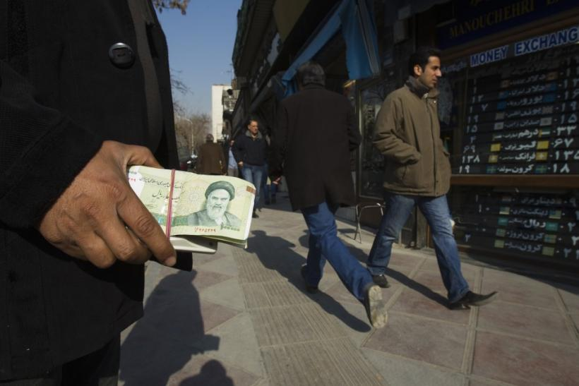 A money changer holds Iranian rial banknotes as he waits for customers in Tehran's business district January 7, 2012.