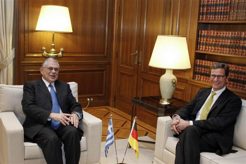 German Foreign Minister Westerwelle talks with Greek Prime Minister Papademos during their meeting in Athens