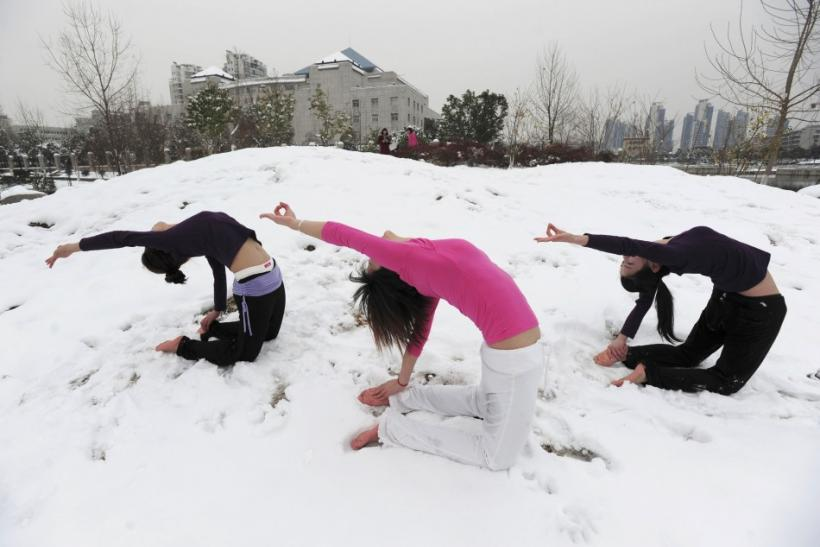 Local residents practise yoga after a snowfall at a park in Wuhan, Hubei province January 6, 2010.