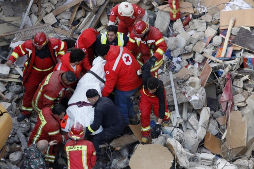 Lebanese Red Cross and Civil Defence personnel transport a dead body found under the debris of a collapsed building in Beirut