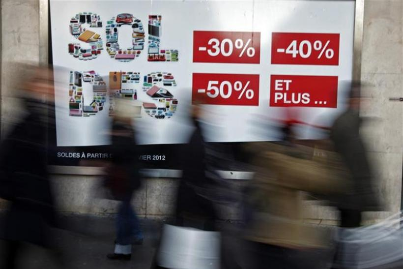 Shoppers walk past a clothing store window advertising sales during the first day of the winter sales in Nice
