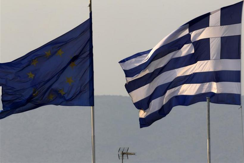A Greek and an EU flag fly over the Greece's Finance Ministry in Athens