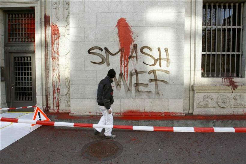 A worker of a cleaning company stands in front graffiti reading 'Smash WEF' on the facade of the Swiss National Bank's building in Zurich