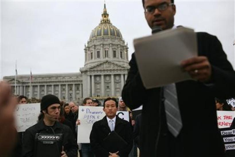 San Francisco Board of Supervisors president David Chiu (c) listens as Jay Nath, the city's chief innovation officer, speaks during a protest of the Stop Online Piracy Act legislation being considered by Congress, at City Hall in San Francisco, Calif