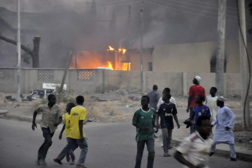 Smoke rises from the police headquarters as people run for safety in Nigeria's northern city of Kano January 20, 2012.