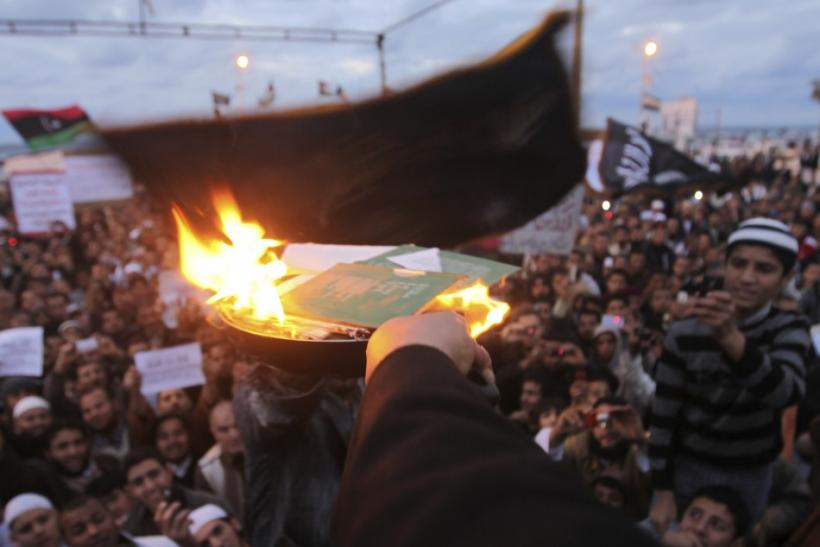 """People burn copies of the """"Green Book,"""" Muammar Gaddafi's eccentric handbook on politics, economics and everyday life, and pictures of Muammar Gaddafi during a demonstration demanding the Libyan National Transitional Council apply Islamic s"""