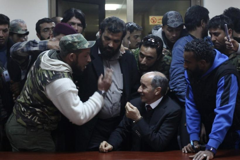 Chairman of the Libyan National Transitional Council (C) Abdul Jalil talks to protesters, who were wounded from the war, at the NTC headquarters in Benghazi January 21, 2012.