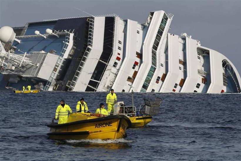 Oil recovery workers pass the Costa Concordia cruise ship