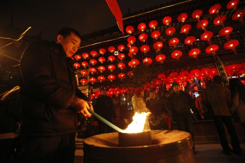 A man lights incense sticks as part of Chinese new year celebrations at the Old City God Temple in Yuyuan Garden in Shanghai