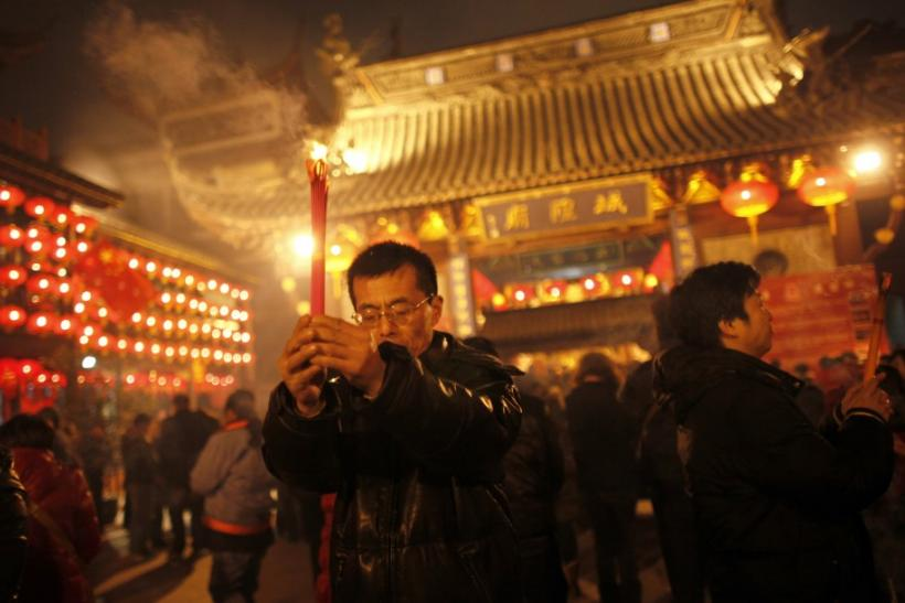 A man holds incense sticks as part of Chinese new year celebrations at the Old City God Temple in Yuyuan Garden in Shanghai