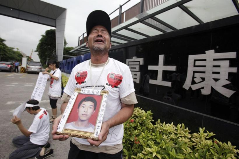 Ma Zishan (C) cries as he carries a portrait of his son Ma Xiangqian outside a Foxconn factory in the township of Longhua, Guangdong province, in this May 29, 2010 file photo. Ma Xiangqian, one of Foxconn's workers, jumped to his death in January.
