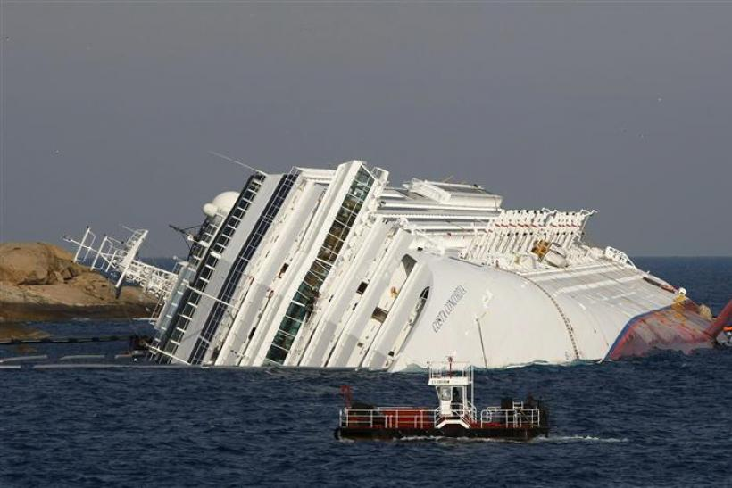 A vessel sails past the cruise liner Costa Concordia, which ran aground off the west coast of Italy, at Giglio island