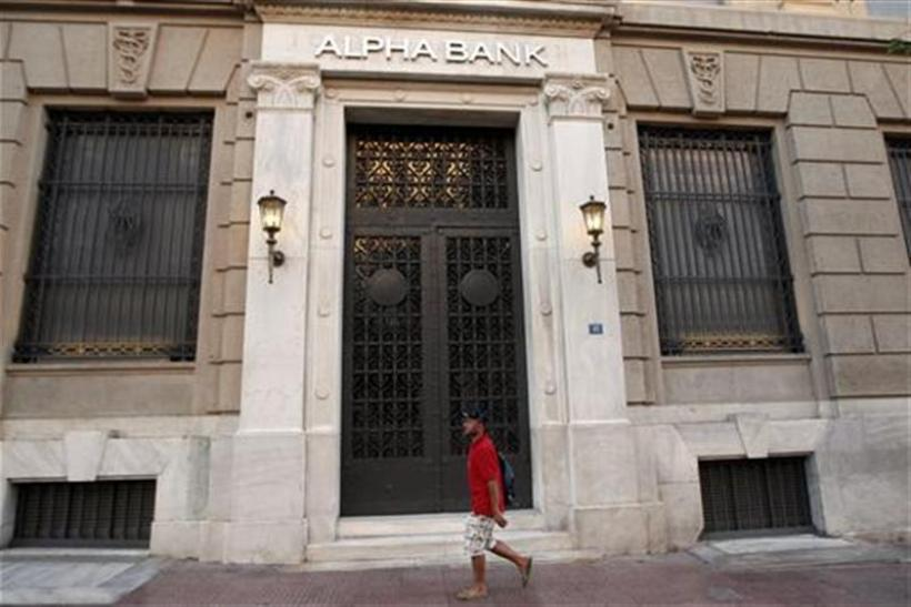 A man walks in front of the headquarters of Alpha Bank in Athens