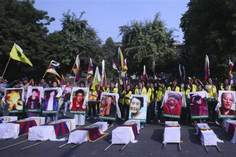 Tibetan exiles holding portraits of Tibetan protesters whom they said were killed during demonstrations in China's Sichuan province, stand behind mock coffins during a protest in New Delhi
