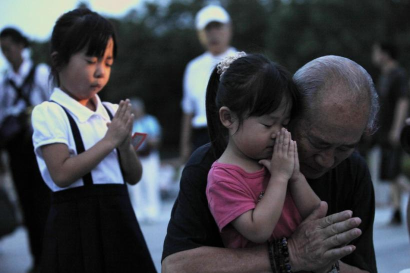A family prays for the victims of the atomic bombing by the U.S., in the Peace Memorial Park in Hiroshima