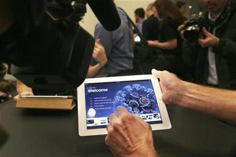 A man shows an example of an iBook textbook on an iPad after a news conference introducing a digital textbook service in New York January 19, 2012.