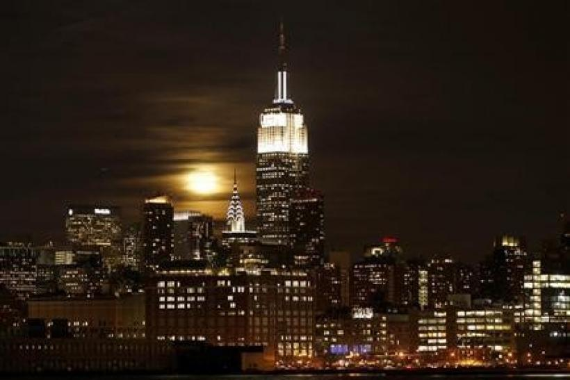 A full moon rises behind the Empire State Building and the Chrysler Building over the skyline of Manhattan in New York