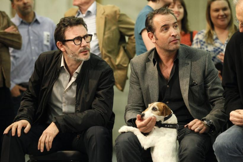 "French actor Jean Dujardin (R) pets the dog Uggie as French director Michel Hazanavicius watches, at a ceremony where the cast and crew of the film ""The Artist"" received the inaugural ""Made in Hollywood"" commendation at Red Studios in"