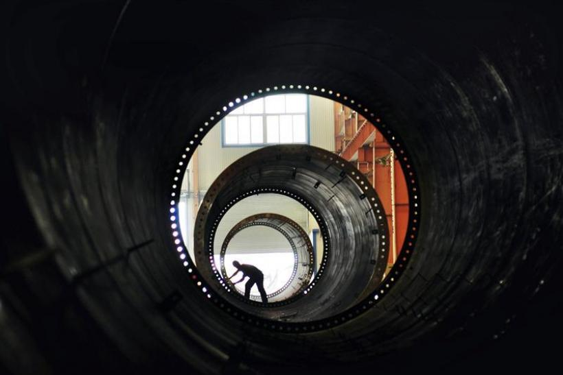 A labourer builds components of wind turbines at a wind power equipment factory in Zouping