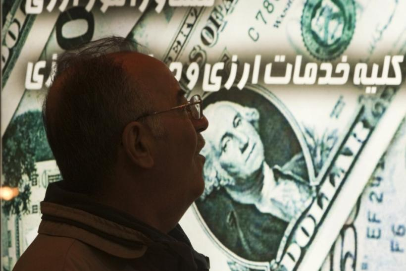 An Iranian man walks past a currency exchange shop in northern Tehran January 3, 2012.