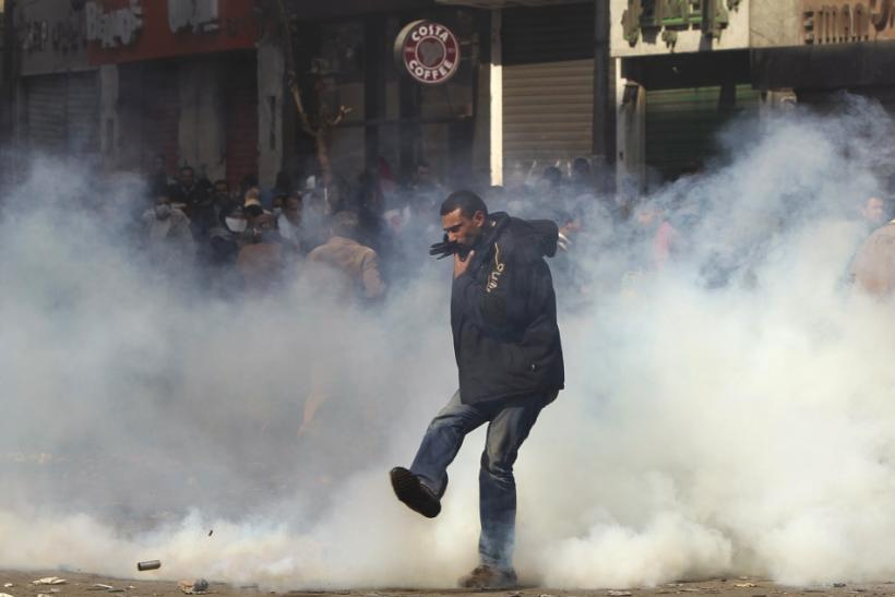 A protester kicks a tear gas canister during clashes with security forces near the Interior Ministry in Cairo February 4, 2012.