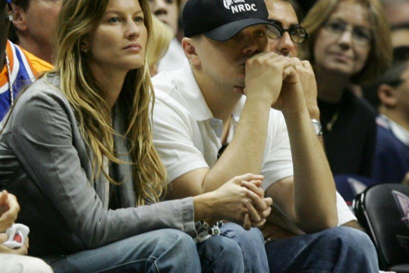 Actor Leonardo DiCaprio (R) and his girlfriend Brazilian supermodel Gisele Bundchen look on from the front row during Game 4 of the NBA Eastern Conference playoff series between the New Jersey Nets and the Miami Heat in East Rutherford, New Jersey