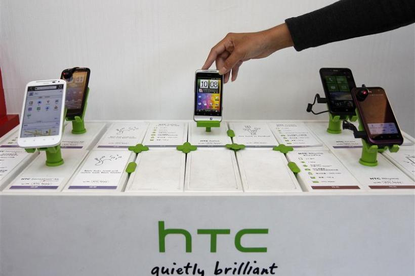 A shop attendant arranges HTC phones in a mobile phone store in Taipei