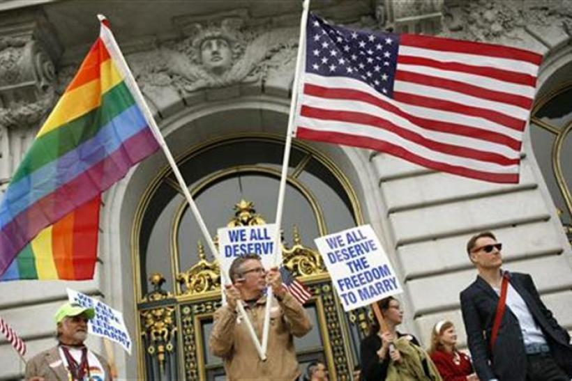 Billy Bradford waves flags outside City Hall after a judge lifted the Proposition 8 stay on same sex marriages at City Hall in San Francisco