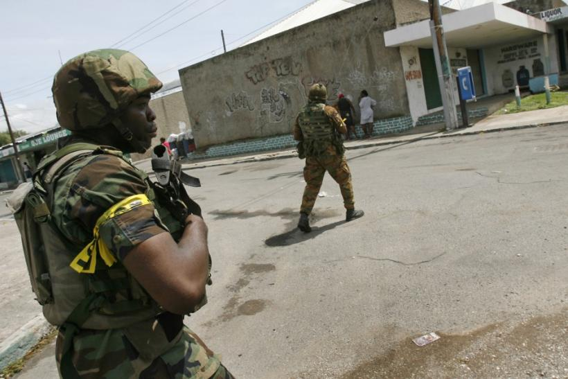 Soldiers patrol a street in the Tivoli Gardens neighborhood of Kingston with foreign journalists escorted into the area