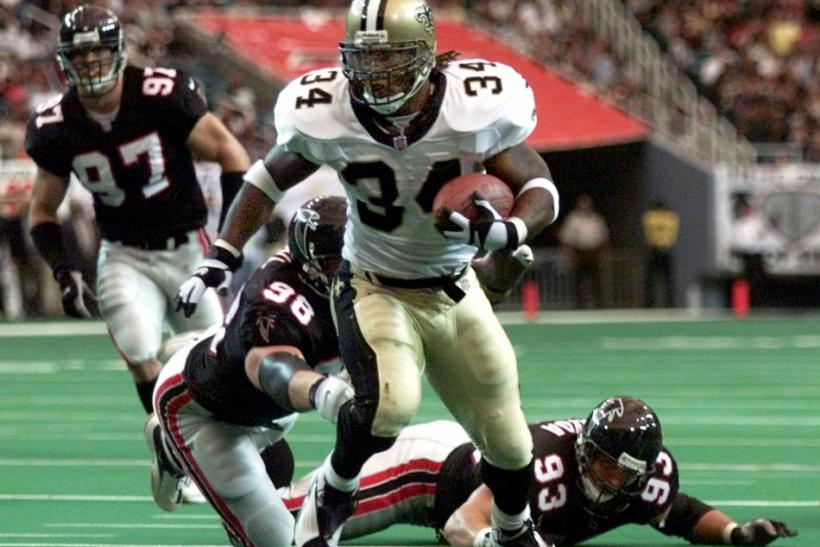 New Orleans Saints' running back Ricky Williams breaks away from Atlanta Falcons' defensive tackles Patrick Kearney (97), Travis Hall (98) and Shawn Sayda (93) on a 12-yard run for a touchdown in the first quarter