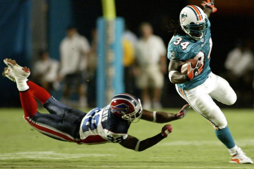 Miami Dolphins' running back Ricky Williams (R) eludes the tackle of Buffalo Bills' defender Nate Clements at Pro Player Stadium in Miami, Florida