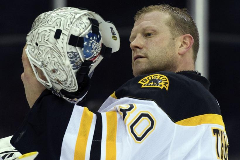 Tim Thomas examines his helmet which has some Tea Party symbols painted on it.