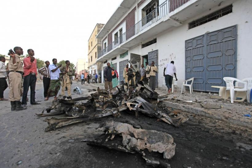 Somali people stand near the scene of a suicide car bomb that exploded leaving scores dead near Muna Hotel in Mogadishu