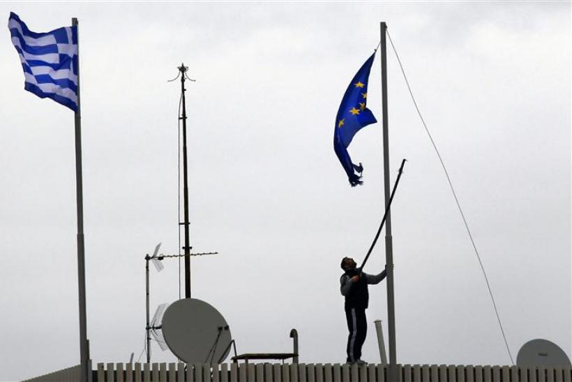 A man tries to replace a torn-off EU flag atop the Greek Ministry of Foreign Affairs in Athens