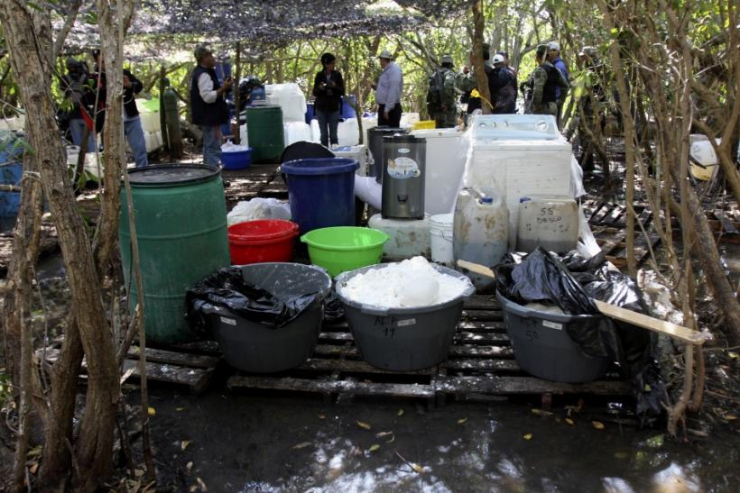 Soldiers and investigators stand near drums and ingredients to make crystal methamphetamines at a clandestine drug processing laboratory