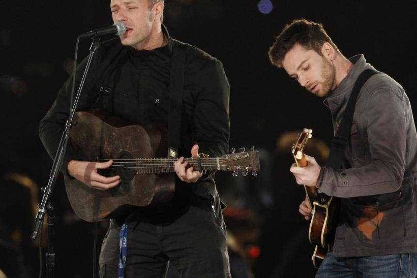 "Chris Martin (L) and Guy Berryman of British band Coldplay perform ""We Can Work It Out"" during the 2012 MusiCares Person of the Year tribute honoring Paul McCartney in Los Angeles, California"